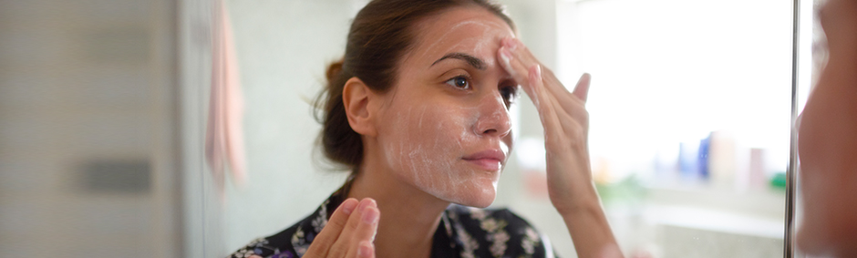 Girl with a cream on her face in front of a mirror