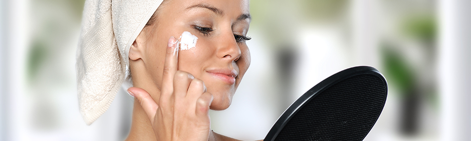 Girl with moisturizer on her face looking on a mirror