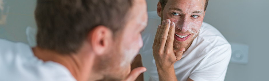A men washing his face in front of a mirror
